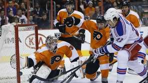 Flyers' Steve Mason reaches for a shot by