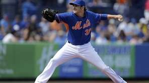 Mets starting pitcher John Lannan throws during the