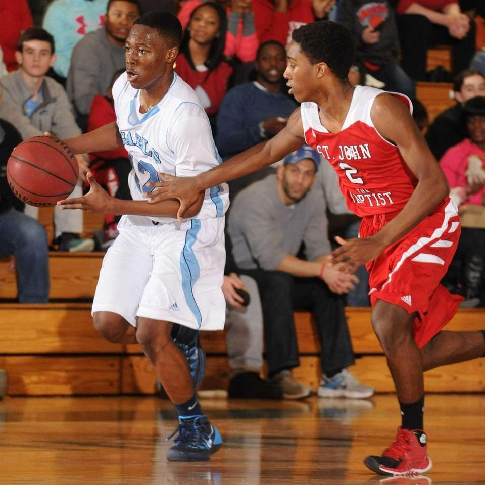 St. Mary's Damani Myers, left, dribbles past St.