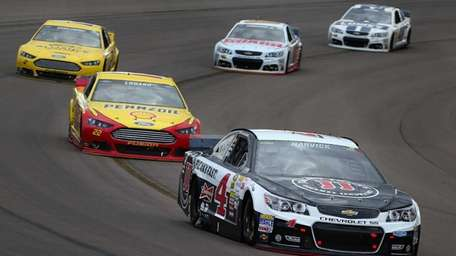 Kevin Harvick leads a pack of cars during