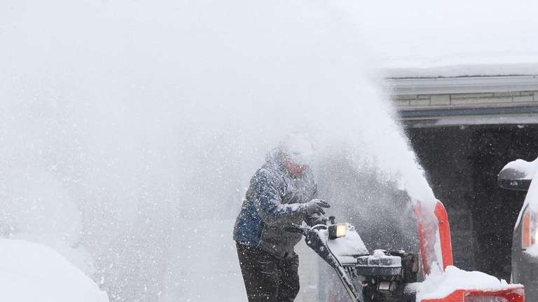 Arlindo Cunha works on clearing his driveway on