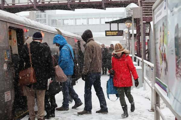 Commuters dodge snowflakes as they wait on platforms