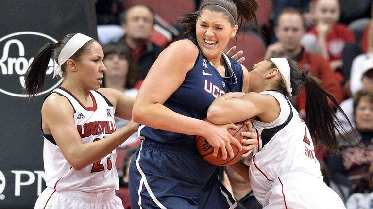 Connecticut's Stefanie Dolson, center, battles Louisville's Tia Gibbs,
