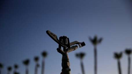 A sprinkler sits idle at a farm on