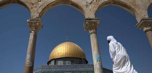 A Palestinian man walks past the Dome of