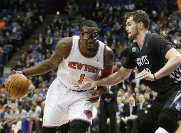 Knicks' Amar'e Stoudemire, left, drives around Minnesota Timberwolves'
