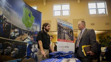 A Schlumberger Ltd. representative, left, speaks with a