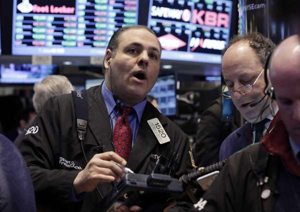 Trader Anthony Riccio, left, works on the floor