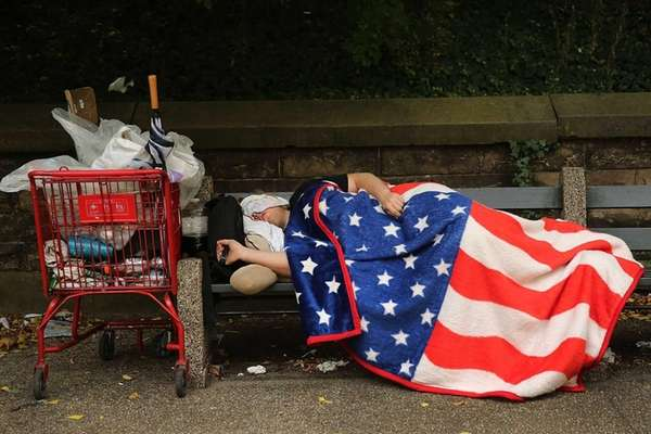 A homeless man sleeps under an American flag