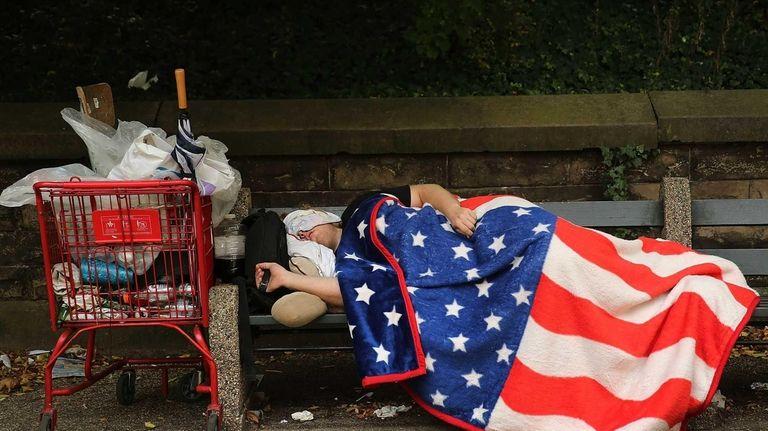 A homeless man sleeps under an American flag