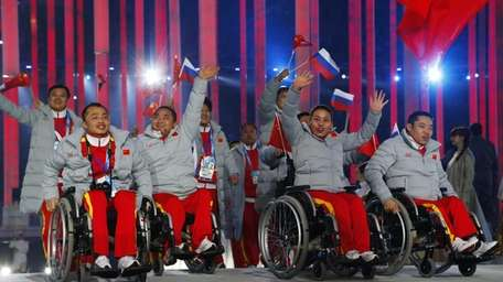 Athletes and officials of China enter the arena