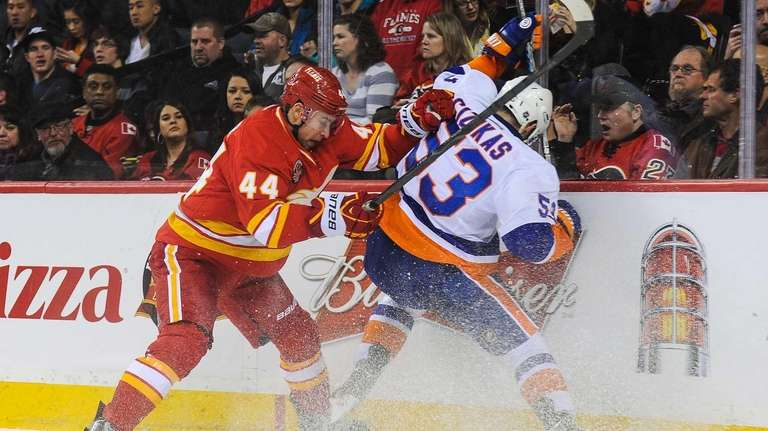 Chris Butler of the Calgary Flames checks Casey
