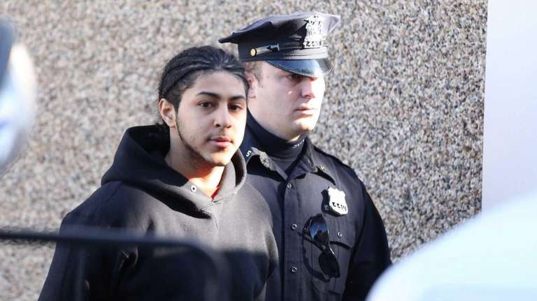 Brandon Davis, 19, of Bridgehampton, is escorted out
