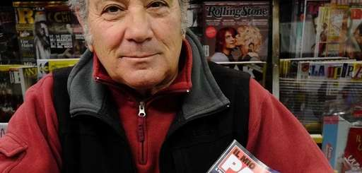 A newsstand vendor holds the new Italian magazine