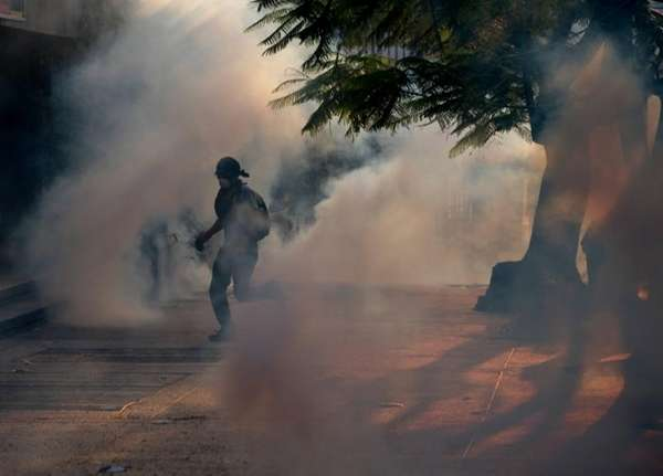 A demonstrator take cover from tear gas fired