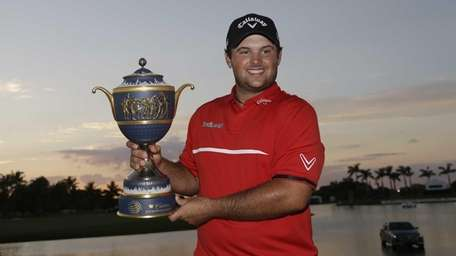 Patrick Reed holds the Gene Sarazen Cup after