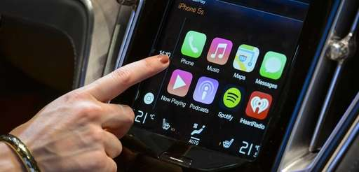A visitor presses the new Apple's CarPlay touch-screen