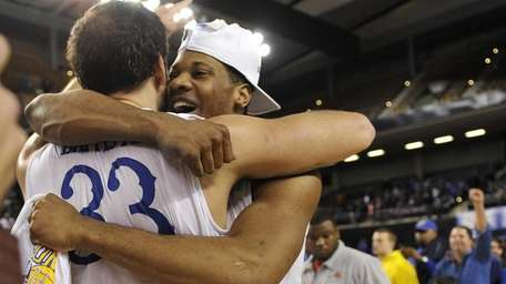 Delaware's Carl Baptiste, left, hugs Marvin King-Davis after
