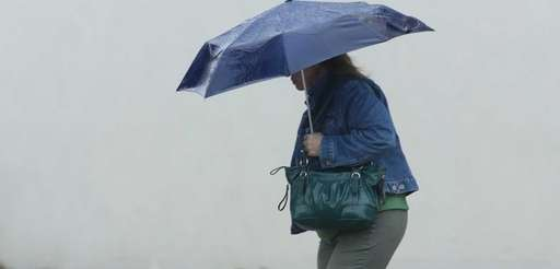 A woman walks in the rain in Smithtown