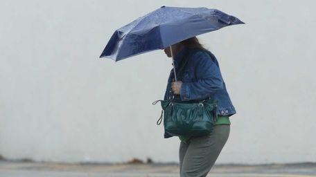 A woman walks in the rain in Smithtown