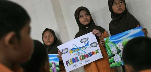 Eight-year-old Syira Nazia Hutabarat, center, shows her drawing