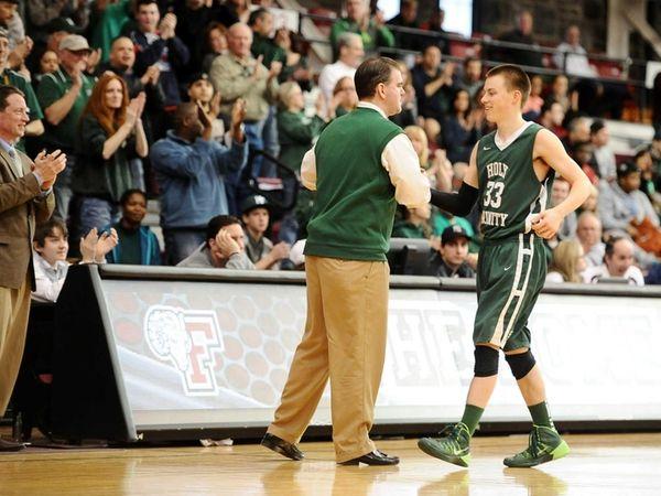Holy Trinity head basketball coach Joe Conefry congratulates
