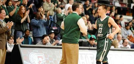 Holy Trinity head basketball coach Joe Conefry congratulates