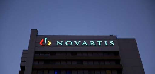 An illuminated logo sits above windows at Novartis