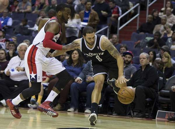 Wizards guard John Wall defends Nets guard Deron