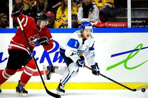 Finland's Henri Ikonen, right, controls the puck chased