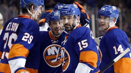 Islander teammates surround right wing Cal Clutterbuck after