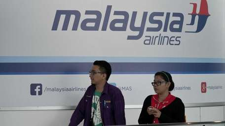 Visitors walks past the Malaysia Airlines logo at
