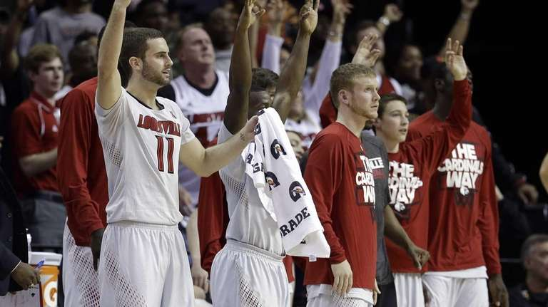 Louisville players watch during the second half of