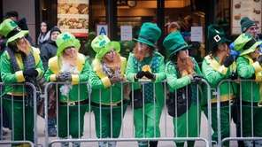 Revelers dressed as leprechauns line the barricades as