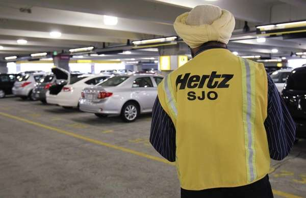 A Hertz rental car worker checks out cars
