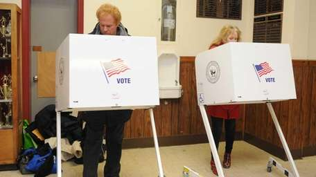 Voters cast their vote in the lobby of Amityville