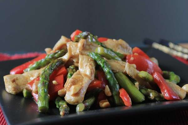 Chicken, asparagus and red peppers are stir fried,