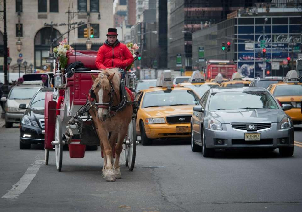A horse-drawn carriage moves along Central Park South,