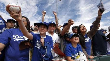 Los Angeles Dodgers fans ask for autographs before