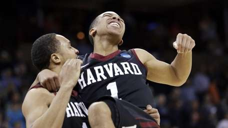 Harvard's Siyani Chambers, right, leaps into the arms