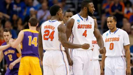 Patric Young reacts with teammate Casey Prather of