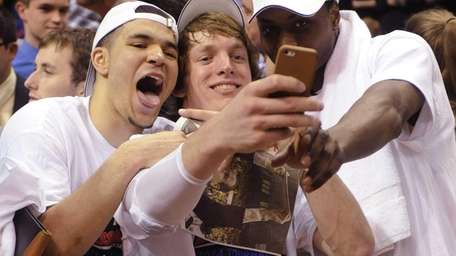 Wichita State's Ron Baker, center, takes a photo
