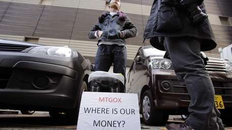Bitcoin trader Kolin Burges stands in protest outside
