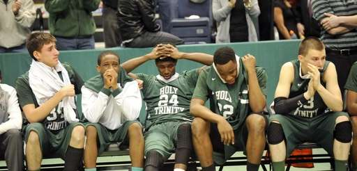 Holy Trinity players react to a 68-52 loss