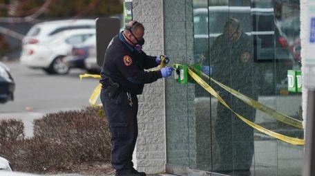 Nassau County police officer dusts for fingerprints after