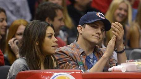 Mila Kunis and Ashton Kutcher watch the Los