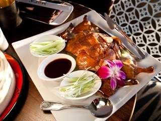 Peking duck, garnished with scallions and cucumbers, is