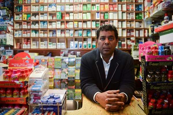 Tarik Ahmed, owner of Locust Valley Tobacco, stands
