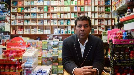 Tarik Ahmed, owner of Locust Valley Tobacco, stands