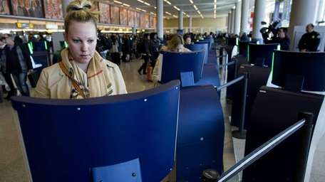 Traveler Liza Leach, of Boston, left, uses an